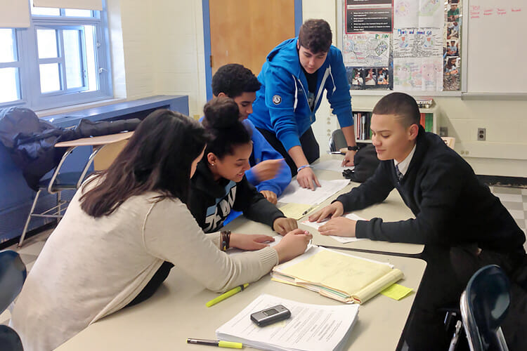 Tenacity Middle School Academy staff work with students in the classroom