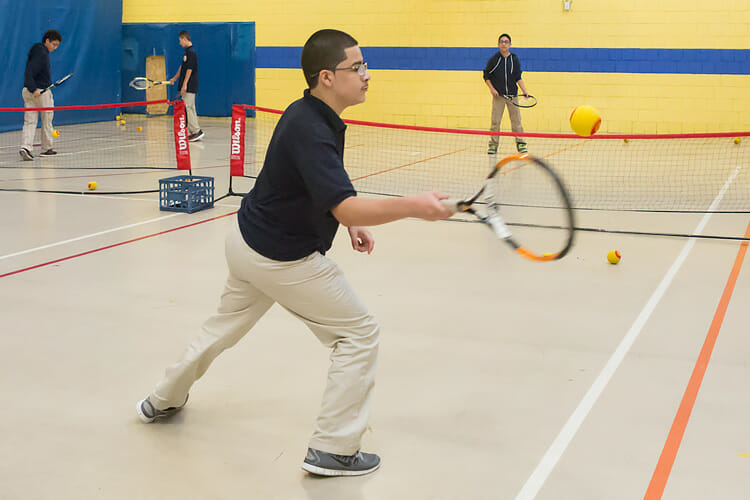 Tenacity Middle School Academy students work on their tennis skills